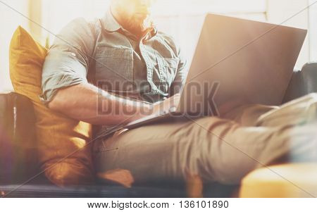 Stylish Hipster working Laptop modern Interior Design Loft Office.Man work Vintage Sofa, Use contemporary Notebook, typing keyboard.Sunny Effect Background.Creative Business Startup Idea.Horizontal, Film