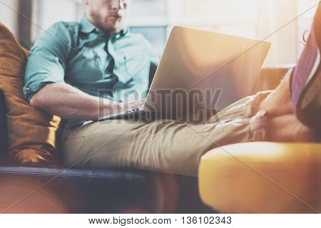 Bearded Hipster working Laptop modern Interior Design Loft Office.Man Work Coworking Studio, Use contemporary Notebook, Typing Message.Blurred Background.Creative Business Startup Idea.Flares effect