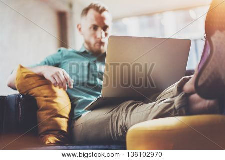 Bearded Hipster working Laptop modern Interior Design Loft Office.Men work Vintage Sofa, Use contemporary Notebook, typing keyboard.Blurred Background.Creative Business Startup Idea.Horizontal, Film