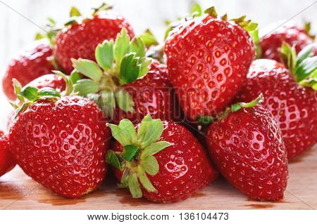 Delicious and sweet red strawberries on a wooden cutting board