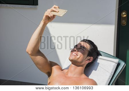 Shirtless Young Man Drying Off in Hot Sun Taking Selfie Picture, Muscular Man Wearing Bathing Suit Sunbathing on Beach Lounge Chair