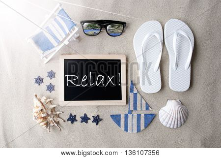 Flat Lay Of Chalkboard On Sandy Background. Sunny Summer Decoration As Holiday Greeting Card. Sand And Beach Environment. English Text Relax