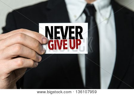 Business man holding a card with the text: Never Give Up