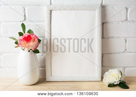 White frame mockup with pink and white roses. Portrait or poster white frame mockup. Empty white frame mockup for design presentation.