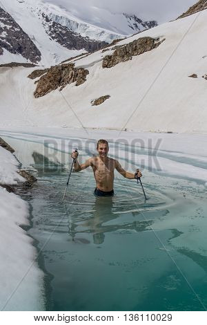 Young man bathing in the ice hole in the mountains