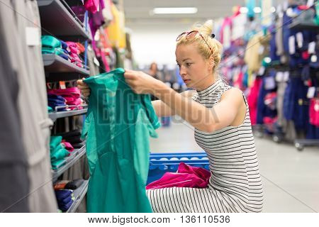 Beautiful caucasian woman shopping sportswear in sports store.