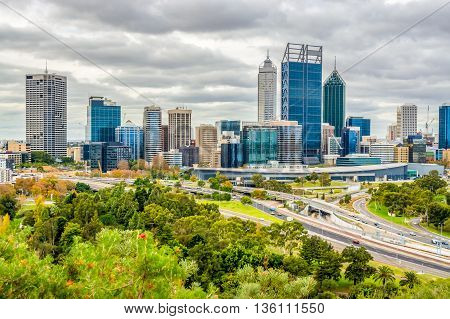Perth city with modern glass buildings towering above the freeway below.