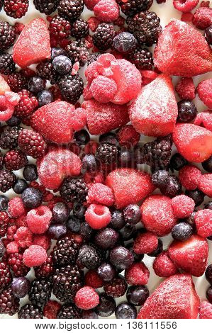 Assorted group of frozen berries as background.