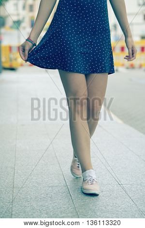 girl legs dressed in a short dress and shoes. Toned photo