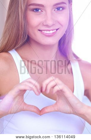 Beautiful woman showing heart shape on her hand , sitting bed