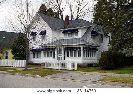 HARBOR SPRINGS, MICHIGAN / UNITED STATES - DECEMBER 24, 2015: A white home with a white picket fence on Third Street in Harbor Springs.