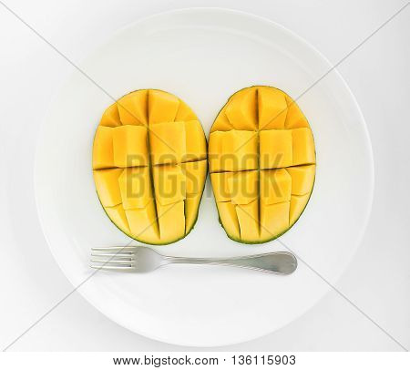 A face made from two mangoes and a fork on a white plate with white background.