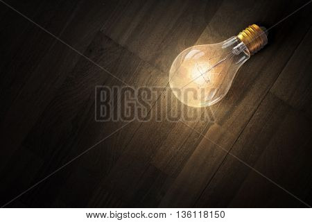 Light bulb on wooden surface . Mixed media