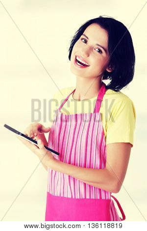 Young woman in pink apron using tablet computer