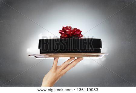 Hand holding tray with gift box . Mixed media