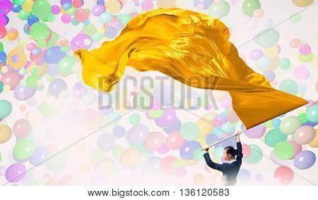 Woman waving yellow flag . Mixed media