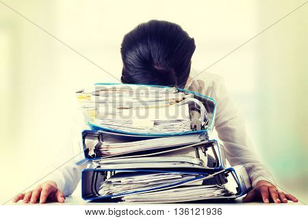 To much work to do. Sad woman with ringbinders