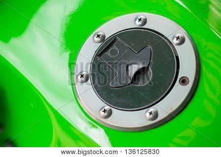 Green motorbike and chrome fuel cap, close up