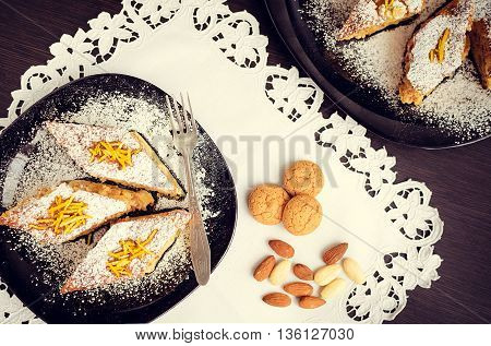 Torta di riso. Baked rice pudding dessert sweetened with sugar powder and garnished with candied orange peels in the top with a fork on the side. Rice cake with almonds cookies and amaretto. Top view.