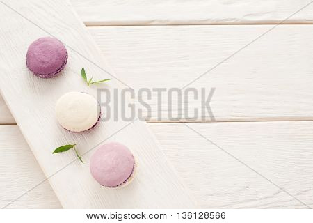 Sweet french macaroons on wood flat lay copyspace. Top voew on set of three purple macaroons on wooden board, lying diagonally on wooden table, void