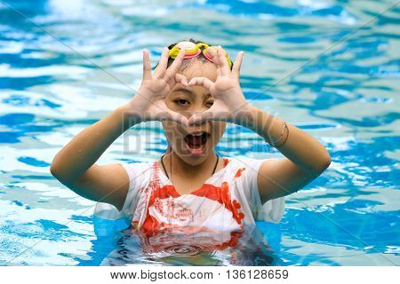 girl in swimming pool with handmade heart shape