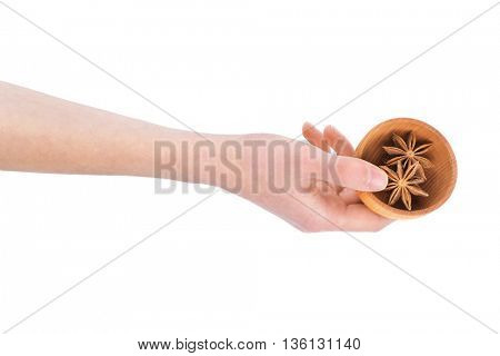 Hand holding wooden bowl with star anise spice isolated on white