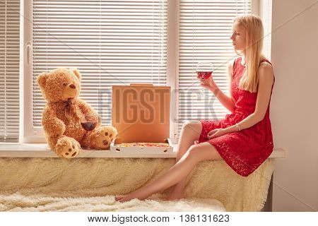 sad blond girl with teddy bear drinking wine with pizza