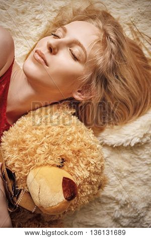 sensual girl lying with teddy bear toned image