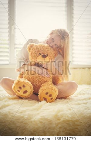 happy girl playing with teddy bear in sun light toned image