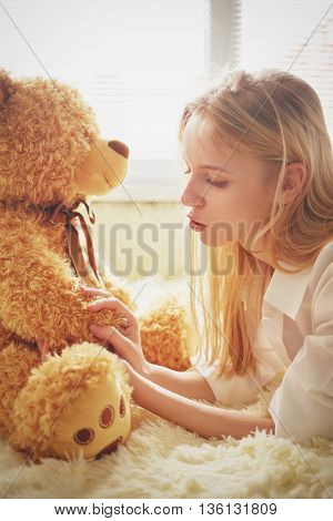 girl playing with teddy bear in sun light toned image