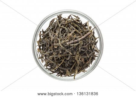 Organic Green Tea (Camellia sinensis) dried long leaves in glass bowl isolated on white background. Macro close up. Top view.