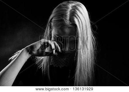 sad woman crying on black background monochrome