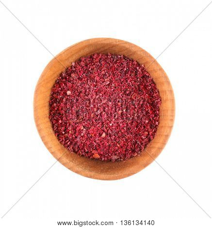 Dried sumac in small wooden bowl isolated on white