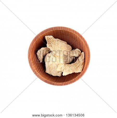 Dried ginger slices in small wooden bowl isolated on white