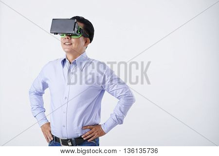 Portrait of smiling Vietnamese businessman in VR glasses