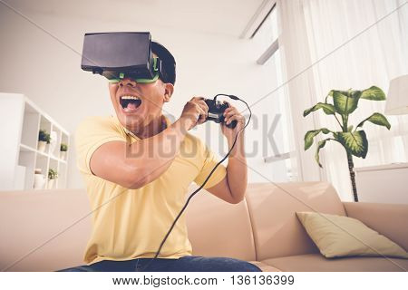 Excited adult man playing videogame at home