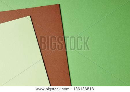 Colored cardboards background in green brown tone. Copy space. Horizontal