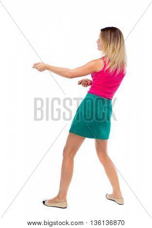 back view of standing girl pulling a rope from the top or cling to something. girl  watching. backside view of person. blonde in a green skirt and pink sweater leaning legs pulls the rope.