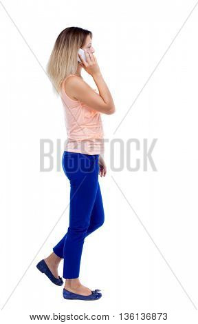 side view of a woman walking with a mobile phone. back view ofgirl in motion.  backside view of person.  Rear view people collection. Blonde in blue trousers is left talking on the white phone.