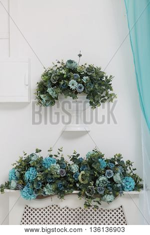 a bouquet of artificial flowers in the vase on the wall