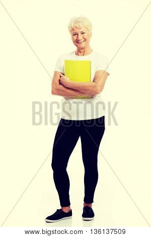 An old woman holding a workbook.