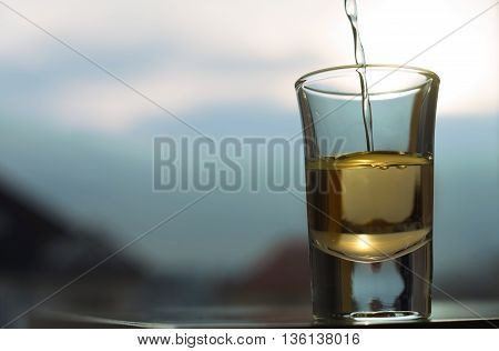 A shot of an alcohol beverage being drunk