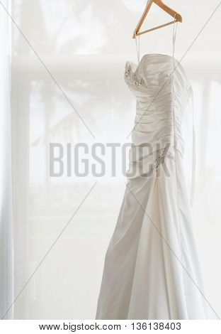 white wedding dress holding near the window