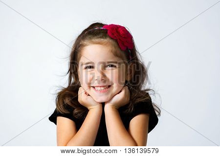 A cute young girl grins with her chin in her hands.