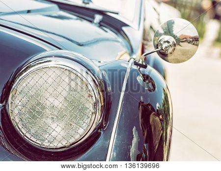 Shiny blue vintage car. Detail view of the headlight. Retro car. Front light. Photo filter. Retro automobile scene. Circle headlamp.