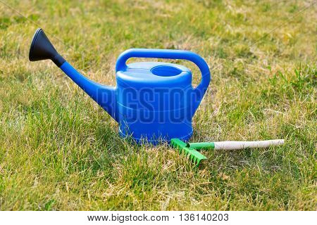 Blue plastic watering can and small rake on the background of green grass. summer in the garden outdoors. Bright equipment care crop