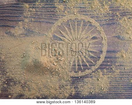 Indian henna powder forms Ashoka Chakra wheel on the textured wooden board