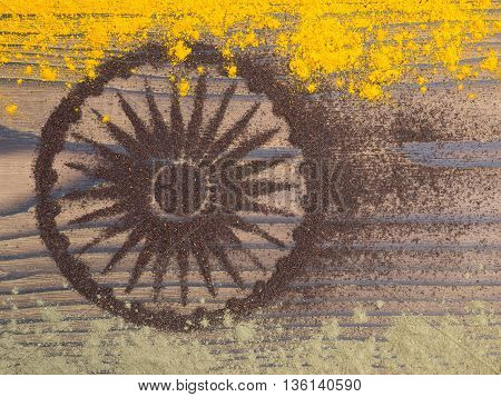 Indian curry and tea powder form India flag on the textured dark wooden board
