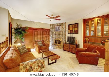 Cozy Upstairs Living Room In Brown Tones With Stone Fireplace In The Corner.
