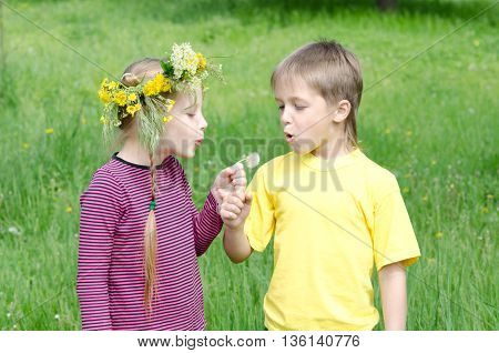 Boy And Girl Standing In Field Blowing Dandelion